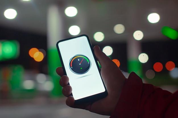 Un homme tient un smartphone avec un compteur de carburant numérique à l'écran dans le contexte d'une station-service de nuit pour une voiture.