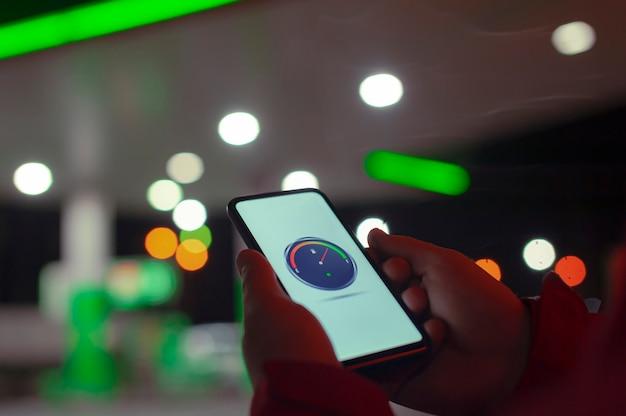 Un homme tient un smartphone avec un compteur de carburant numérique sur l'écran