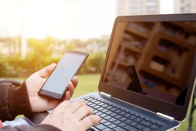 L'homme tient le smartphone dans la main avec l'aide d'un ordinateur portable.