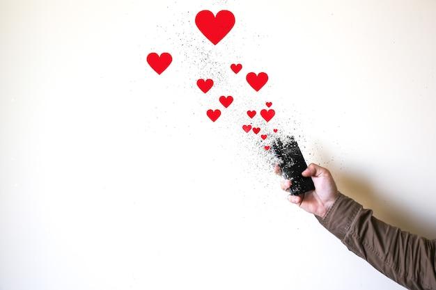 L'homme tient le smartphone dans les mains isolés sur fond blanc. smartphone tombant en morceaux. coeurs et likes des réseaux sociaux. accro aux technologies.