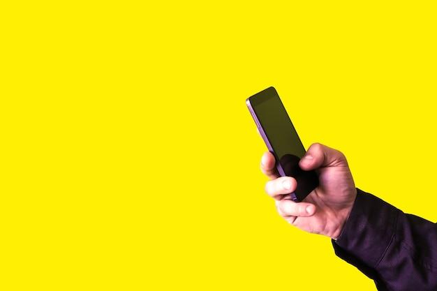 L'homme tient le smartphone dans les mains isolés sur fond jaune. accro aux technologies.