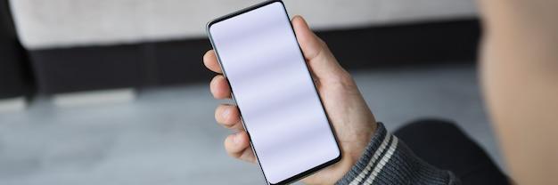 L'homme tient le smartphone avec l'écran blanc dans sa main