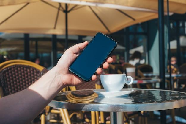 L'homme tient un smartphone et une tasse de café dans un restaurant.