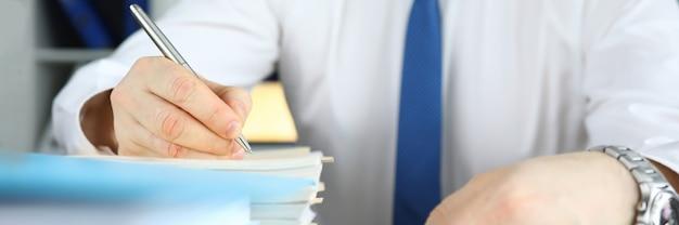L'homme tient un stylo et écrit dans une grosse pile de documents à son bureau