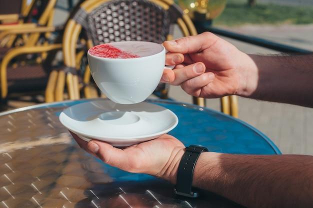 Un homme tient une tasse de café au restaurant.