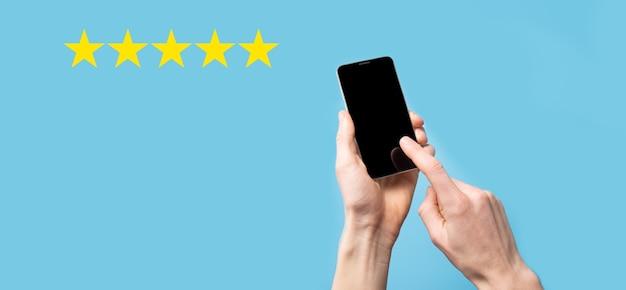 L'homme tient le téléphone intelligent dans les mains et donne une note positive, icône symbole cinq étoiles pour augmenter l'évaluation du concept d'entreprise sur la surface bleue