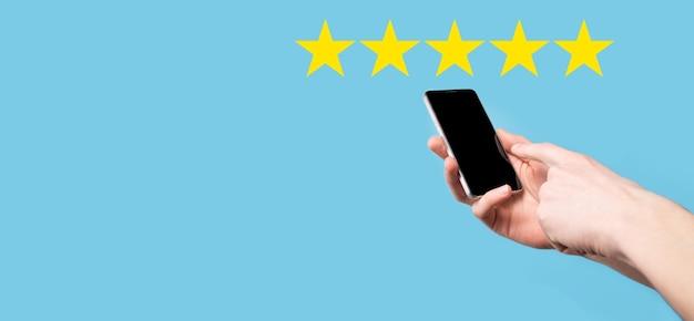 L'homme tient le téléphone intelligent dans les mains et donne une note positive, icône symbole cinq étoiles pour augmenter la note du concept d'entreprise sur fond bleu.expérience du service client et enquête de satisfaction des entreprises.