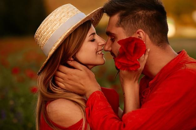Homme tient tendre belle femme debout avec elle sur le champ vert avec des coquelicots rouges