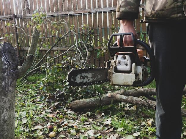 Un homme tient une tronçonneuse professionnelle dans ses mains, il est prêt à scier des arbres dans le jardin