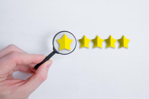 Un homme tient un verre comme une loupe sur une note abstraite de cinq étoiles sur un blanc. analyse des notes. meilleur score. mise à plat.