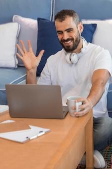 Homme de tir moyen agitant à l'ordinateur portable
