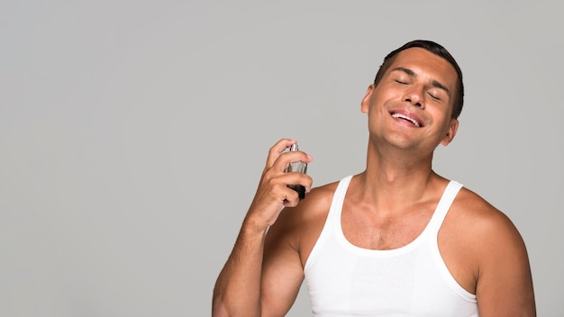 Homme de tir moyen à l'aide de parfum