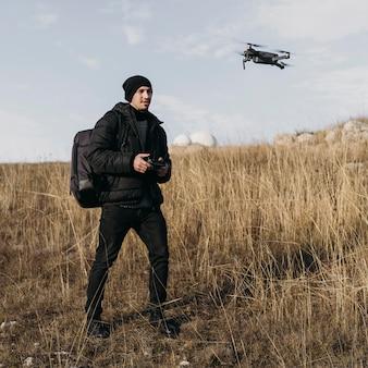 Homme de tir moyen contrôlant le drone
