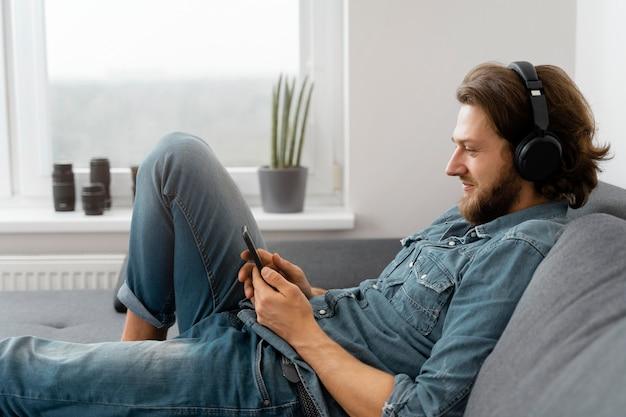 Homme de tir moyen avec des écouteurs sur le canapé