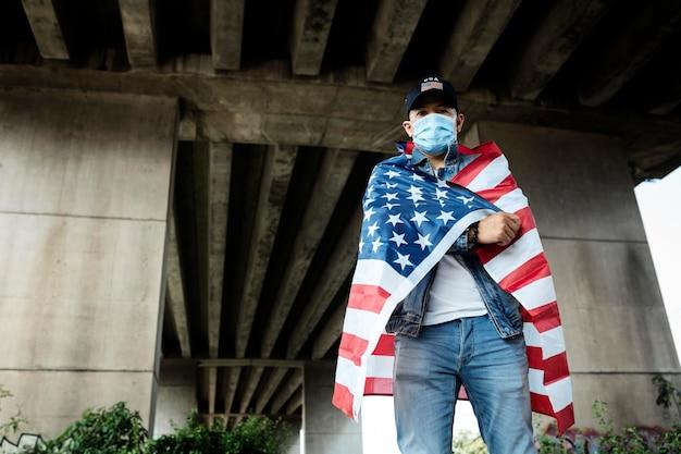 Homme de tir moyen portant un masque facial