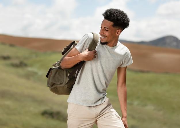 Homme de tir moyen portant sac à dos