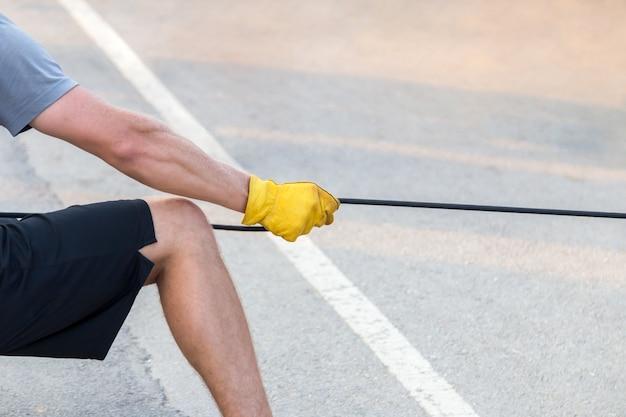 Homme tirant la corde avec un gant jaune