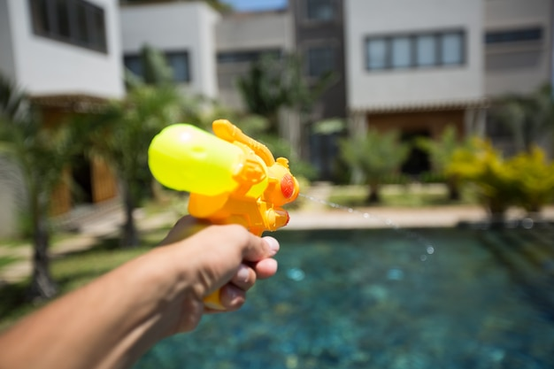 L'homme tire un pistolet à eau sur une femme tout en s'amusant dans la piscine
