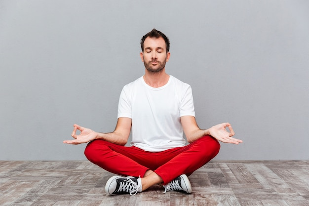 L'homme en tissu décontracté assis en position du lotus sur fond gris