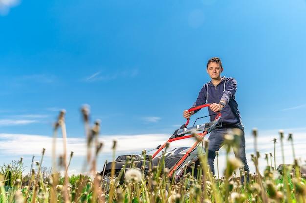 L'homme tond la pelouse avec une tondeuse à gazon