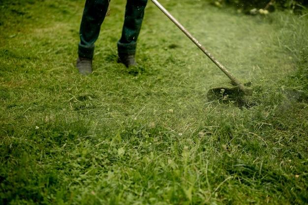 Homme tondant l'herbe, la tondeuse se bouchent.