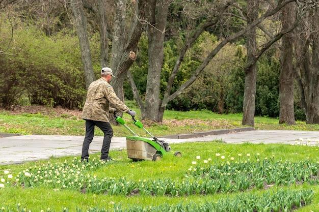 Un homme avec une tondeuse à gazon tond l'herbe dans le parc