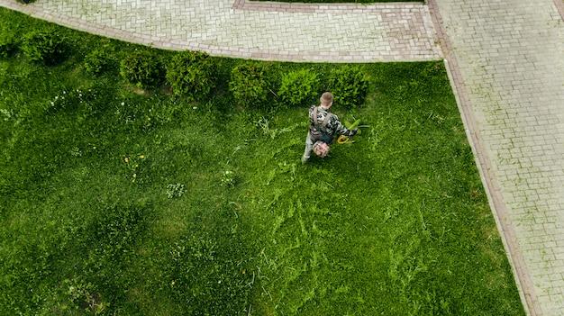 L'homme tondeuse tond la pelouse la vue du haut