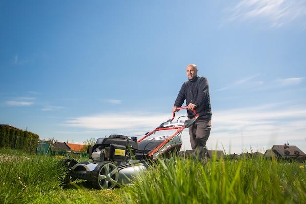 Homme tondre, couper l'herbe sur son immense jardin, champ vert par la tondeuse de jardin à moteur, concept de jardinage