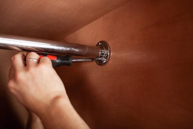Un homme tord un tuyau pour un cintre dans un placard avec un tournevis.