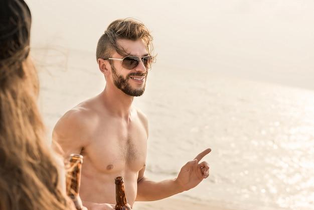 Homme torse nu avec un ami ayant parti et buvant à la plage