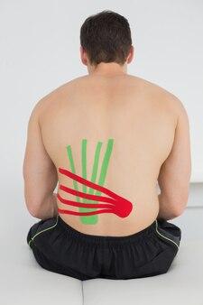 Homme torse nu avec des bandes de kinesio rouges et vertes au dos
