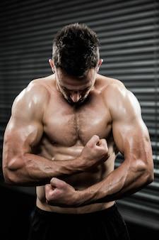 Homme torse nu, fléchissant les bras à la salle de gym