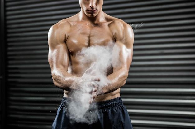 Homme torse nu en frappant des mains avec du talc à la salle de gym crossfit