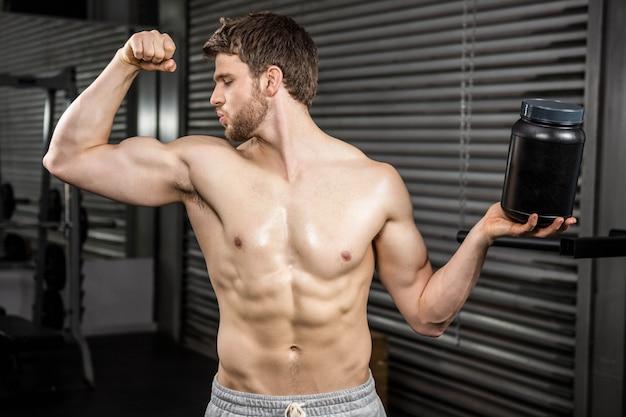 Homme torse nu montrant des biceps et tenant une canette au gymnase de crossfit