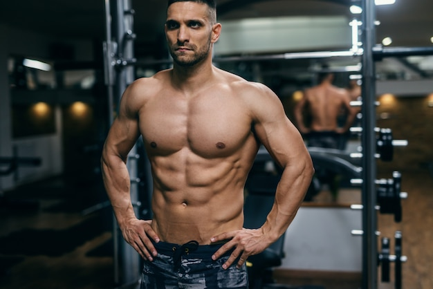 Homme torse nu musclé avec les mains sur les hanches posant dans une salle de sport
