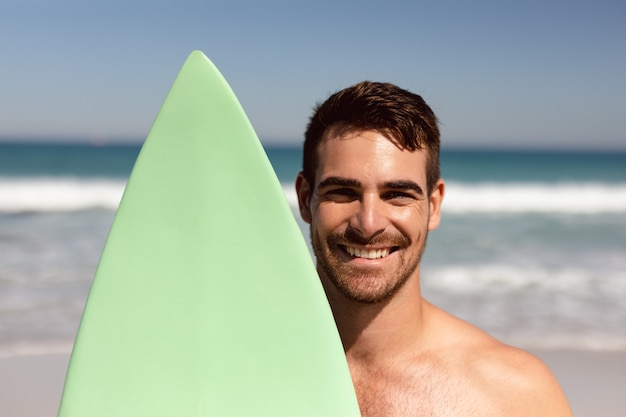 Homme torse nu avec planche de surf en regardant la caméra sur la plage au soleil