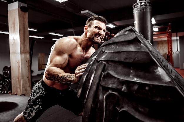Homme torse nu renversant un pneu lourd