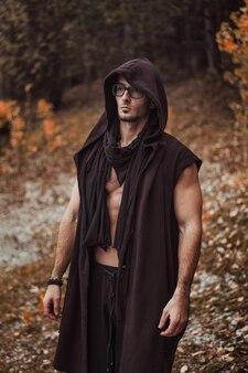 Un homme avec un torse nu se dresse sur la forêt d'automne