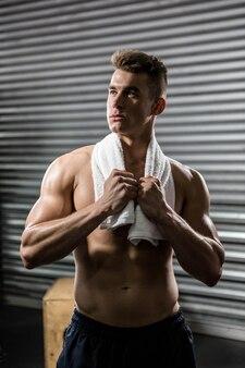 Homme torse nu avec une serviette autour du cou au gymnase