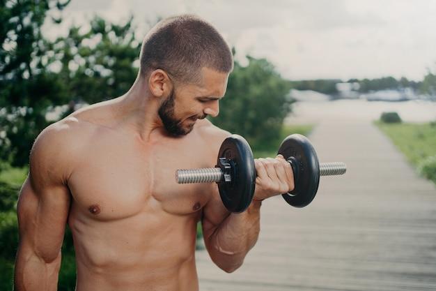 Homme torse nu travaillant à l'extérieur avec des poids