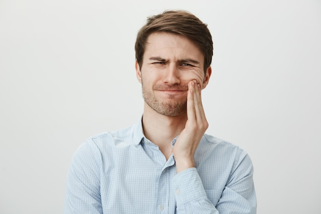 Homme touchant la joue et grimaçant de douleur de mal de dents