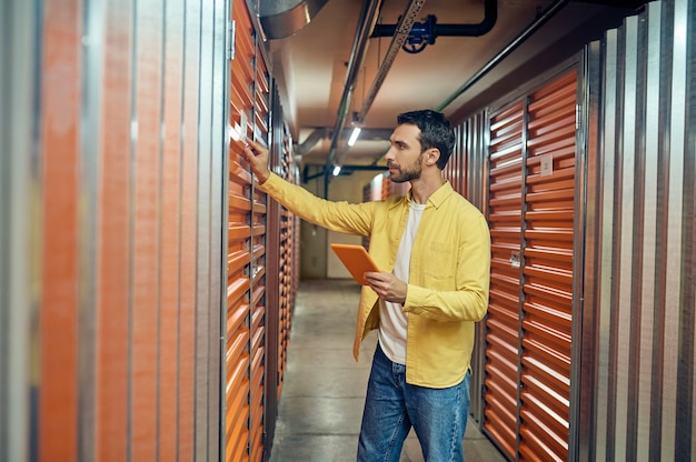 Homme touchant la porte de garage dans la salle de stockage