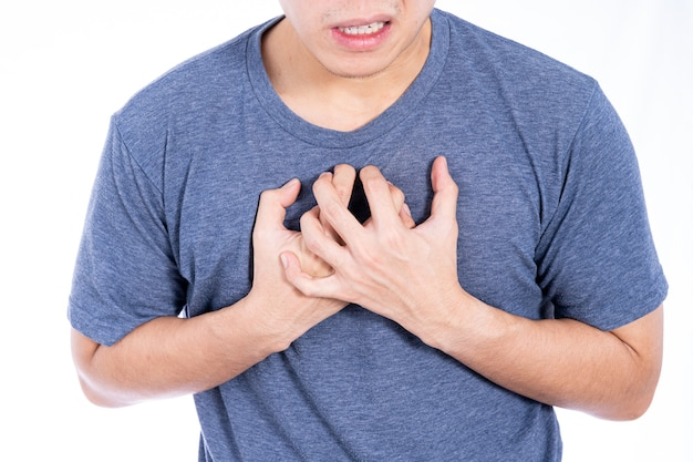 Homme touchant son coeur ou poitrine isolé mur blanc.