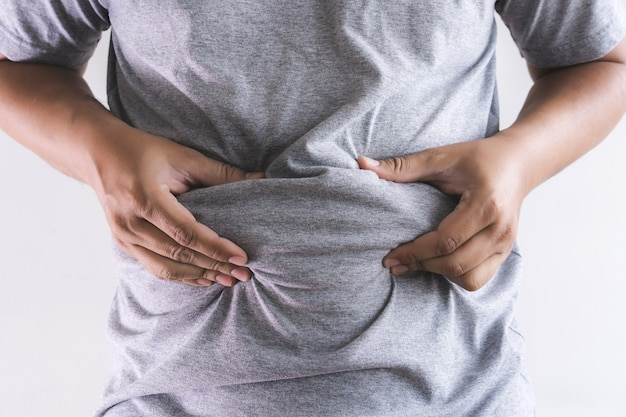 Homme touchant son gros ventre potelé