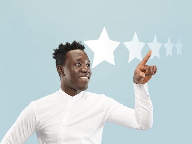 Homme touchant le symbole cinq étoiles pour augmenter la note de l'entreprise, de l'application ou du service. laisse son tarif pour produit, spécialiste, programme. concept d'entreprise, technologie, marketing, publicité, vente, communication.