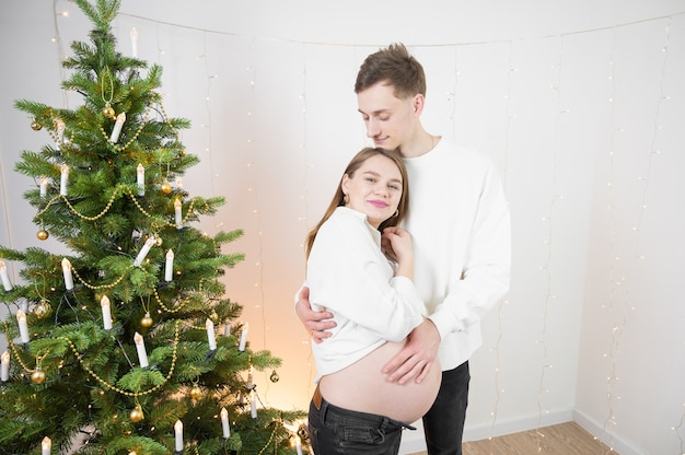 Homme touchant le ventre de sa femme enceinte. heureux jeune couple à noël.