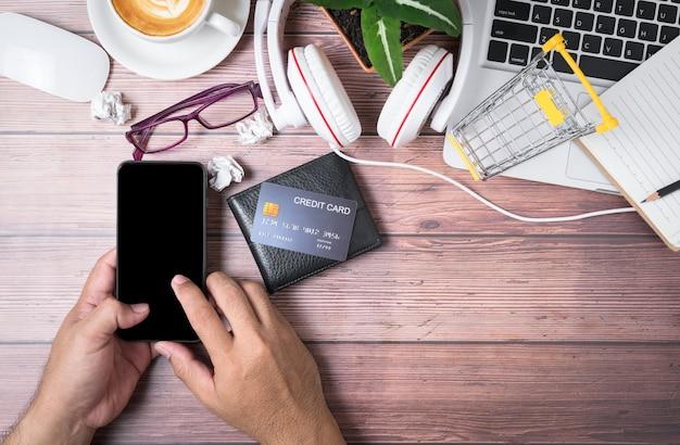 L'homme touche sur écran noir téléphone mobile avec carte de crédit sur portefeuille et ordinateur portable sur bois