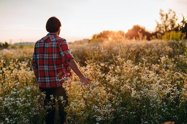 L'homme touche ses fleurs de la main dans le champ.