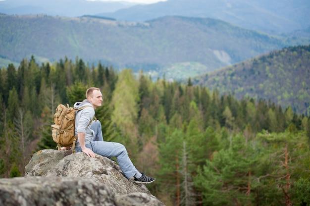 Homme de tourisme courageux assis au sommet d'un rocher, avec une vue imprenable étonnante sur la vallée de la forêt et les collines