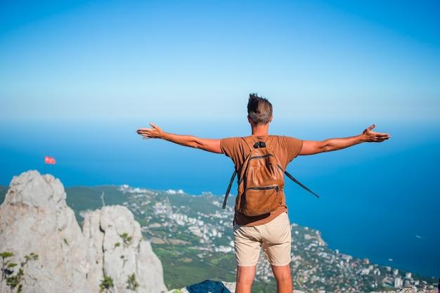 Homme de tourisme en plein air sur le bord de la falaise au bord de la mer